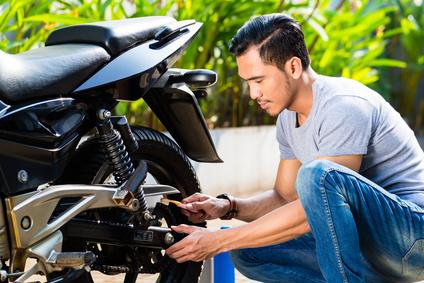 Asian man doing motorcycle maintenance in his garden