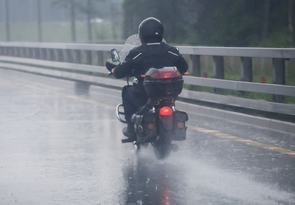 62930155 - motorcyclist moves on motorcycle on highway to rainy weather